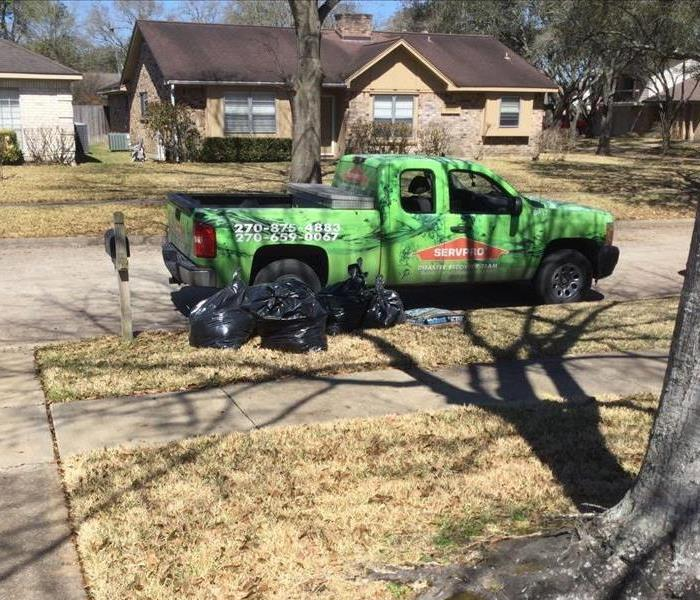 Green SERVPRO truck sitting in a neighborhood, parked on the curb with black bags of garbage sitting around